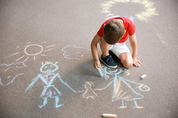 Little child drawing family with chalk on asphalt