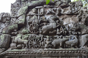 Ancient temple stone carved bas-relief in Angkor Wat. Hinduist god in carriage bas-relief closeup. Angkor Wat temple
