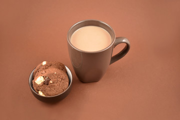 Cookies with chocolate milk stock images. Biscuits on a brown background. Cup of chocolate milk with snack. Cup of chocolate milk with biscuits