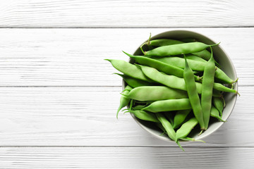 Bowl with fresh green beans on wooden table, top view