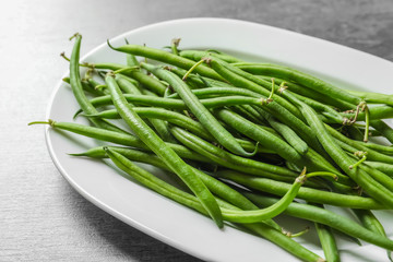 Plate with fresh green French beans on table, closeup