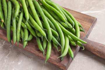 Wooden board with fresh green French beans on table