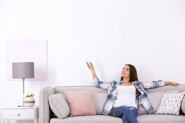 Young woman switching on air conditioner while sitting on sofa near white wall
