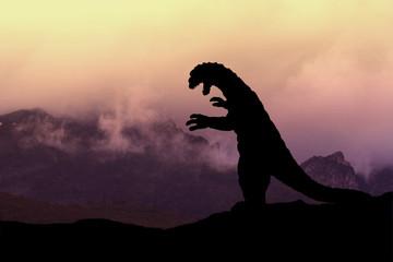 Silhouette eines Godzilla-artigen Monsters in einer Vulkanlandschaft Fotoväggar