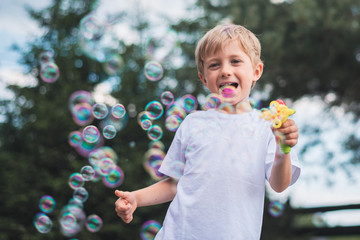 5-6 years old boy play with soap bubbles