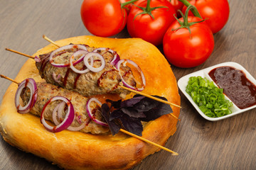 Lulya-kebab. Shish kebab on a stick, minced meat. Traditional Caucasian dish. On a cutting board, with green salad, ketchup, spices