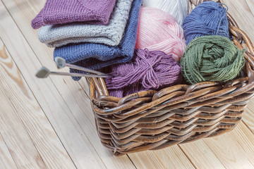 basket with threads and knitting needles and knitted sweaters