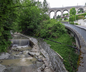 Classic Swiss scene at Pully, near Lausanne with flowing River, Viaduct and lush green trees