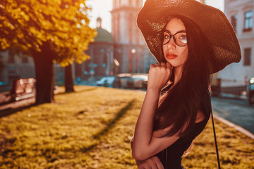 Stylish young woman posing in the city. Fashionable outfit. Beautiful model wearing classic clothing and accessories