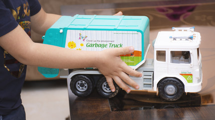 little boy holds with his hands a garbage truck toy
