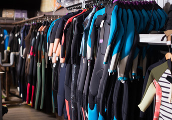 Image of colorful wetsuit hanging in the  store for surfing