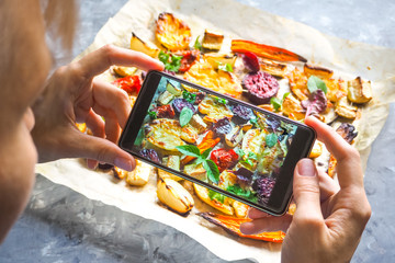 Taking photo of vegetables on a hot baking sheet.