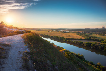 Beautiful nature landscape panorama at sunset time. View from chalk hill or mountain to green meadows and fields with river and nuclear power plant far away. Summer travel tranquil background