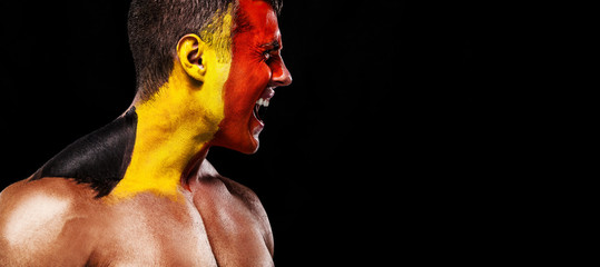 Soccer or football fan with bodyart on face with agression - flag of Belgium.