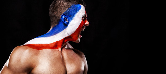 Soccer or football fan with bodyart on face with agression - flag of France.