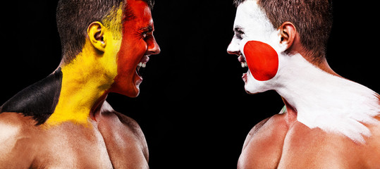 Soccer or football fan with bodyart on face with agression - flag of Belgium vs Japan.