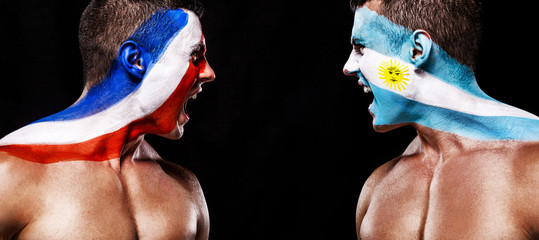 Soccer or football fan with bodyart on face with agression - flag of France vs Argentina.