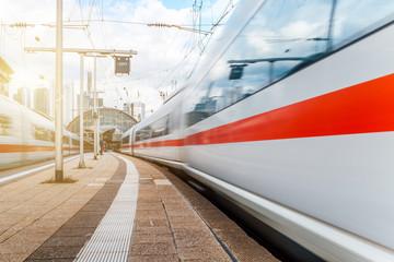 Fotobehang Spoorlijn Bahn fährt bei Sonnenschein vom Bahnhof ab