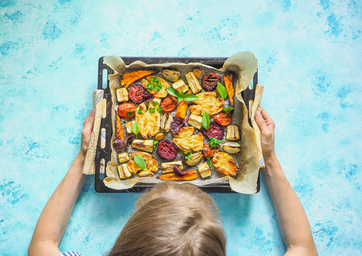 Baked vegetables on a baking sheet in the women's hands.