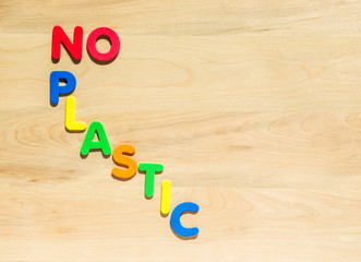 "colorful foam letters spelling the words ""No Plastic"" on a wooden table with copy space"