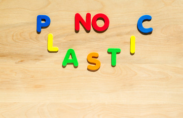 "colorful foam letters spelling the words ""No Plastic"" on a wooden table"