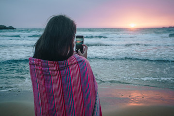 Rear view of young brunette woman in pink towel standing on the beach near the sea with smartphone and making photos of beautiful pink and purple sunset.