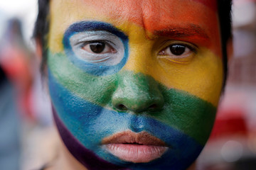 An activist with his face painted in the colours of the rainbow flag participates in a march organized by the LGBT community in Managua