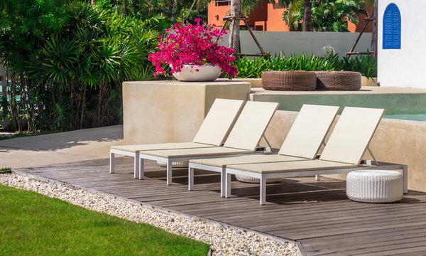 Sunbathing lounger swimming pool side./ Sunbathing lounger swimming pool side and flower pot on summer.