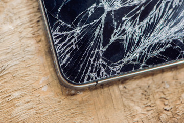 Smartphone display with broken glass on a wodden table