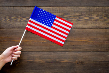 American flag concept. Hand hold small flag on dark wooden background top view copy space
