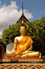 Golden buddha statue in saffron robes sitting in the lotus position
