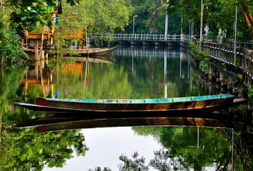 Old rustic wooden boat on a calm backwater canal in Asia. the was is calm and shows a perfect mirror image reflection.