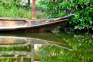 Bow of an old wooden boat moored against a grassy bank, showing a perfect mirror image reflection in the water
