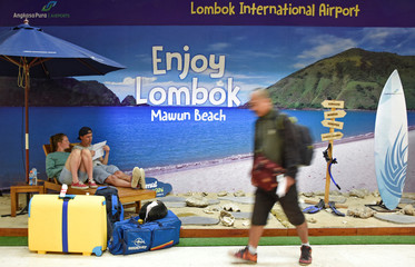Foreign tourists sit at a photo booth at Lombok International airport as their flight to Bali was canceledled due to Mount Agung's eruption