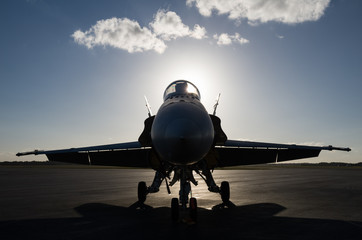 Military fighter jet in silhouette on runway