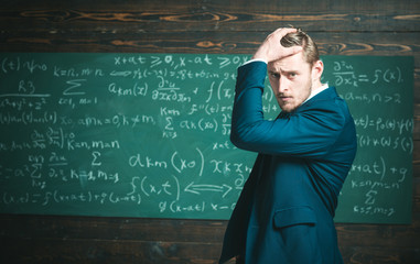 Unproven theorem. Man formal wear classic suit looks smart, chalkboard background. Genius suffers unresolved mathematics problem. Man formal wear work on theorem, chalkboard with equations background