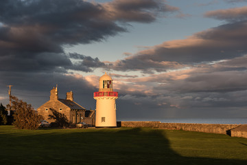 Ballinacourty lighthouse lit by the setting sun with the sea and dark clouds in the background. Ballinacourty, County Waterford, Republic of Ireland.