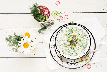 Cold soup with fresh cucumbers, radishes with yoghurt in bowl on wooden background. Traditional russian food - okroshka. Vegetarian meal. Top view. Flat lay