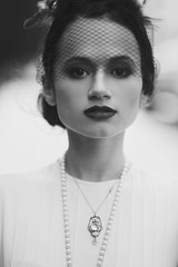 Black and white portrait of a stunning woman dressed in 30s style