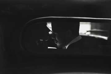Dreamy picture of a kissing couple dressed in 30's style and sitting in the car