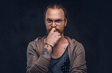 Smart pensive redhead hipster with full beard and glasses dressed in casual clothes, poses with hand on chin in a studio. Isolated on a dark background.