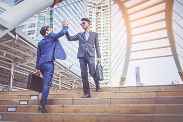 Two Businessman giving high five at city