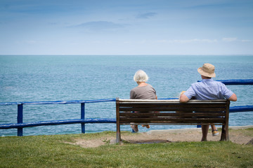 Elderly couple relaxing in front of the sea view. With copyspace above.