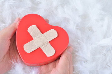 Red heart on white feather