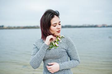 Portrait of brunette girl in gray dress background the lake.