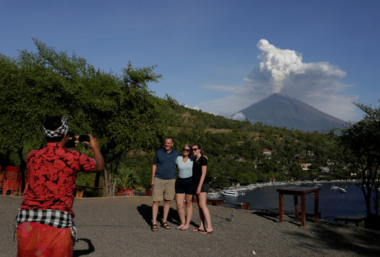 A guide take pictures of foreign tourists with Mount Agung volcano's eruption in the background, seen from Amed in Karangasem Regency