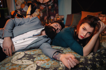 Handsome bearded man in business suit lying on young pretty sexy woman. Businessman with beard resting at home after hard work day. Entrepreneur sleeps in comfortable hotel room after long air flight