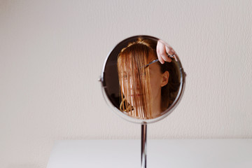 Ginger woman cuts her hair. Reflection in the mirror. Minimal concept
