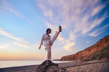 samurai in a kimono while training on the ocean coast, at sunrise. The concept of a healthy lifestyle, unity with nature, meditation.