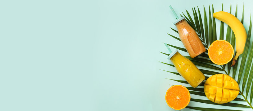 Exotic orange, banana, pineapple, mango smoothie and juicy fruits on palm leaves over blue background. Banner. Detox summer drink. Organic fruits and vegan concept. Top view, flat lay, copy space